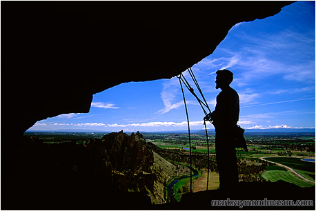 Lifestyle photograph showing a silhouetted climber standing under an overhanging cliff