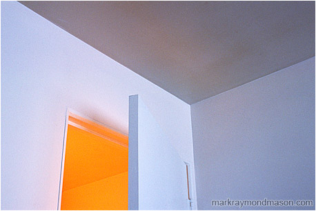 Abstract photograph showing a partly open doorway with contrasted white, blue and yellow light