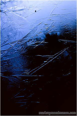 Abstract nature photograph of dark patterns in the ice of a frozen lake