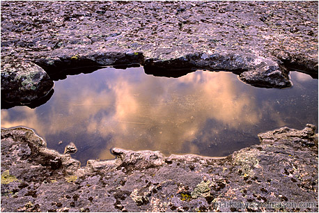 Fine art photograph of reflections in a pool of water, surrounded by textured rock