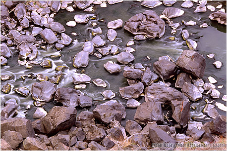 Fine art photograph showing water flowing around river rocks at the bottom of a basalt canyon