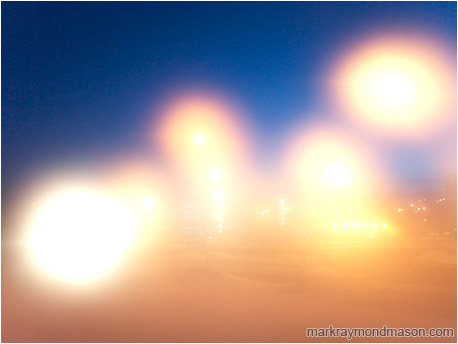 Abstract photograph of street lamps and lens flare against a dark night sky