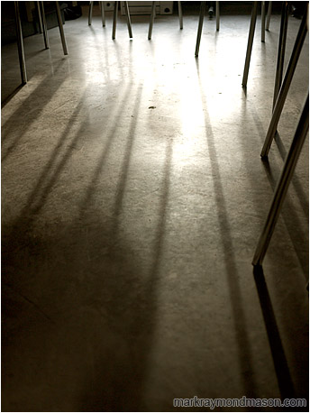 Abstract photograph of intertwined chair legs, silhouetted in a pool of light on a concrete floor