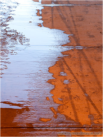Abstract photo of a red concrete walkway covered in ice, water and tire tracks