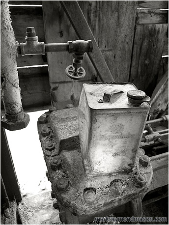 Fine art black and white photograph showing a petrol can inside the remains of an ancient excavator