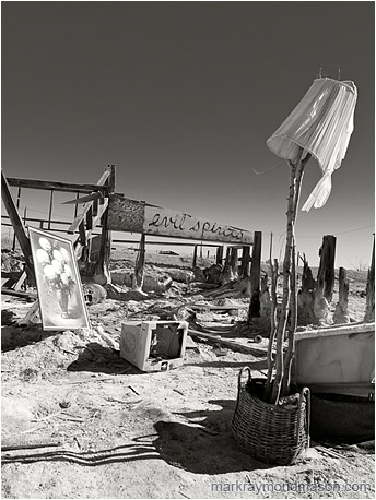 Fine art B&W photograph showing the remains of a structure and scattered objects on a salt flat