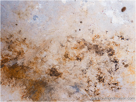 Abstract photograph showing stormy-looking stains on the surface of a plastic picnic table
