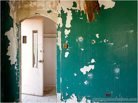 Fine art photograph of an archway and a slack door, set behind a peeling, pitted, bizarrely painted wall
