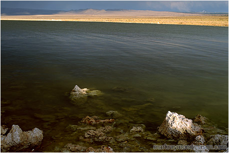 Fine art photograph of small volcanic rocks in a large lake, with stormclouds and sunshine in the distance