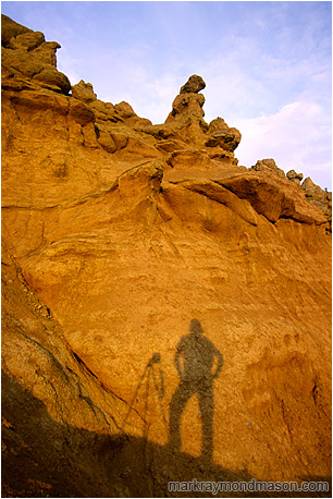 Landscape photograph of a silhouetted photographer and camera mounted tripod against a dramatic sculpted hoodoo background