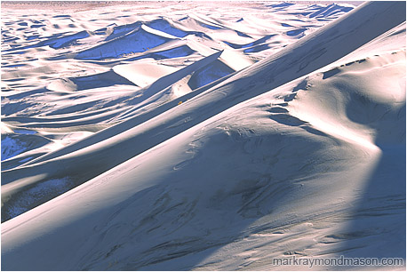 Abstract photograph of huge sand dunes, snow, and shadows deep in the desert