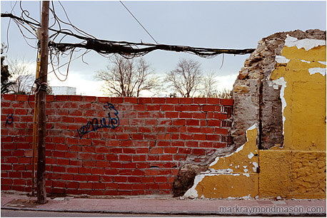 Fine art photograph of tangled wires, broken bricks, graffiti, and chipped plaster