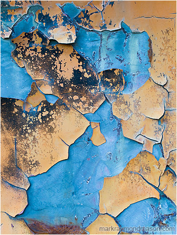 Abstract macro photograph showing large chunks of peeling orange paint falling away to reveal cool, blue-tinted metal beneath