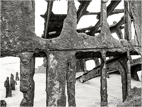 Fine art black and white photograph of the metal skeleton of an old wrecked ship, surrounded by pale, ocean-worn sand.