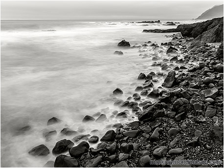 Long exposure black and white photo of water crashing and receding on a beach littered with shiny rocks