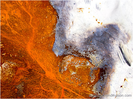 Fine art abstract photo showing rusted metal and chipped paint curving together like a shoreline on a lake
