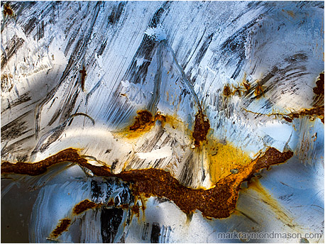 Abstract photograph showing painted metal, kinked and rusted, looking like the peak of a volcano covered in snow