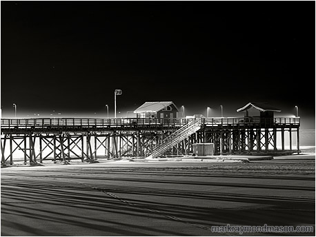 Fine art black and white photograph showing a thin shroud of fog around a lone snow-lined wharf on a black winter night