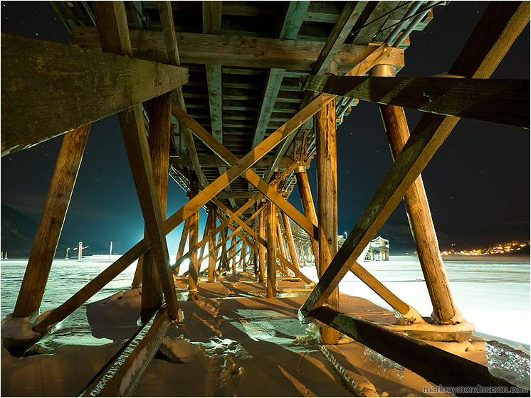 Beams, Ice, Night Sky: Salmon Arm, BC, Canada (2016-12-30) - Fine art photograph showing giant beams on the underside of a wharf, frozen in ice, set against a night sky with faint stars