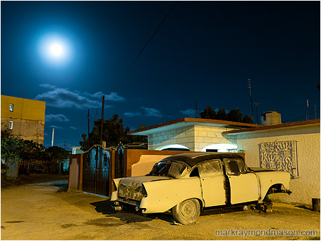 Fine art photograph showing an ancient car propped on blocks in the night with a hazy full moon in the background