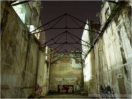 Fine art photograph showing a vacant urban canyon between concrete buildings, with exposed trusses against a starry sky