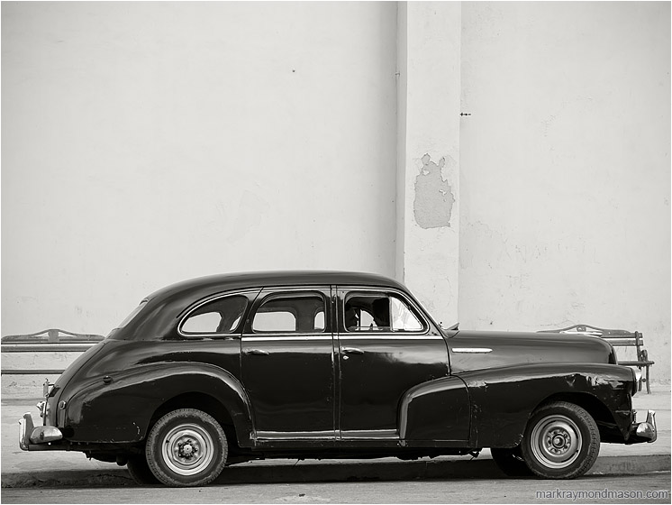 Parked Car, Silhouettes: Havana, Cuba (2017-02-15) - Fine art black and white photograph showing silhouetted lovers in a battered 1950s model car, parked beside a plain concrete wall