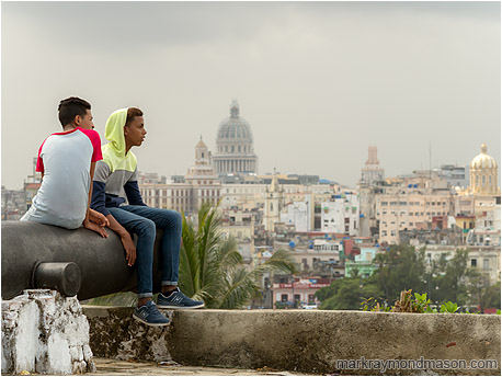Fine art photograph showing two teenage boys sitting on an ancient cannon, the Havana skyline and grey skies in the background