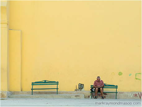 Fine art travel photo of a man seated alone on a bench in front of a towering orange wall
