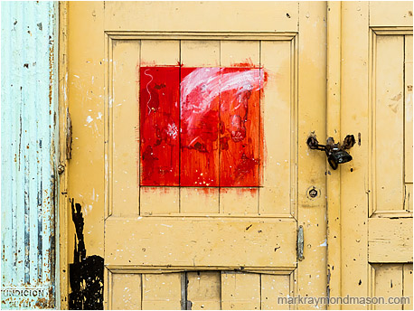Fine art abstract photograph showing a red painted square, like a framed picture, in the middle of an ageing wooden door