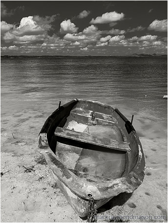 Fine art black and white photograph showing a flooded boat, cocked sideways, sitting abandoned on the silty shores of a shallow lake