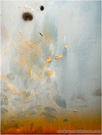 Abstract fine art photo of burnt orange paint leaping upward like flames on a charred and scratched shop door