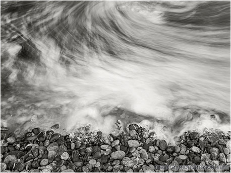 Fine art black and white long-exposure photograph showing moving water swirling like fog around seaside stones