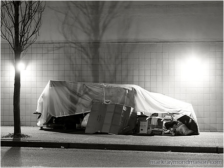 Black and white photograph of a homeless person sleeping in a crude tarp and cardboard shelter against a tile wall